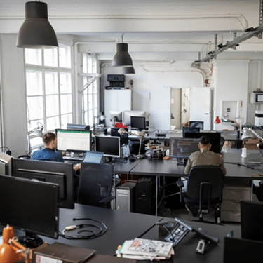 View of modern office with people at desks, business IT Panancea Solutions